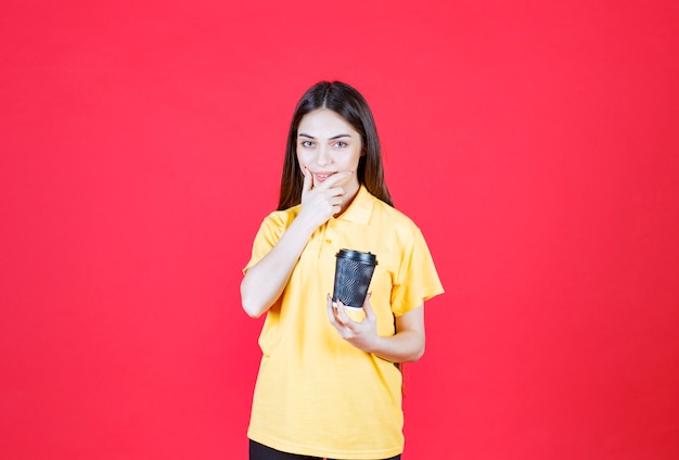 Frau im gelben hemd, die eine schwarze einwegkaffeetasse hält, nachdenkt und eine gute idee hat.
