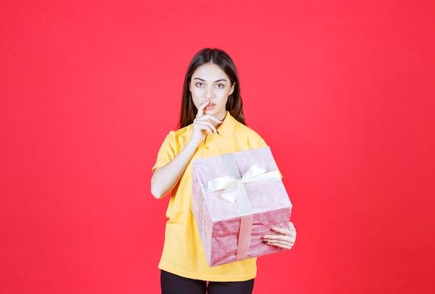 Frau im gelben hemd hält eine rosa geschenkbox und sieht verwirrt und zögerlich aus.