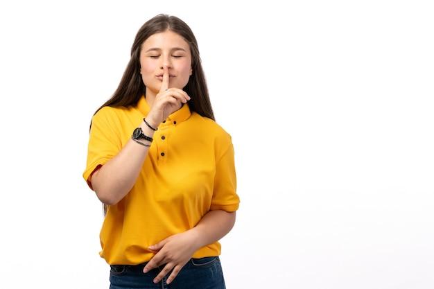 Frau im gelben hemd und in den blauen jeans, die auf der weißen hintergrundfrauenmodellkleidung posieren und lächeln