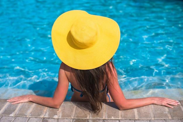 Frau im gelben hut, der am swimmingpool sich entspannt