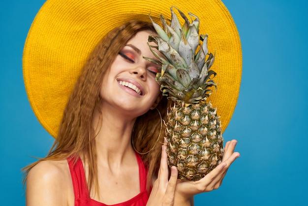 Frau im gelben hut mit ananas in den händen emotionen spaß lebensstil sommerfrucht blau.