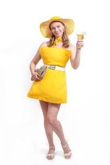 Frau im gelben kissenkleid, hut mit geldbörse und cocktailglas lächelt auf weißem hintergrund. sommerkonzept. pillow challenge wegen isolation zu hause bleiben.