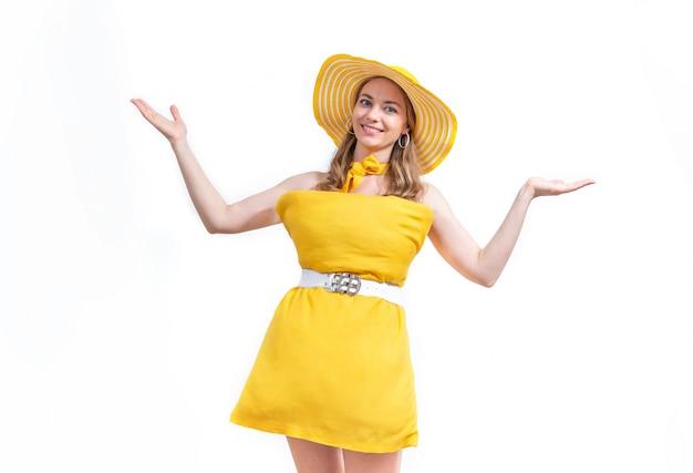 Frau im gelben kissenkleid und im hut lächelt und spreizt ihre arme zu seiten gegen weißen hintergrund. pillow challenge wegen isolation zu hause bleiben.