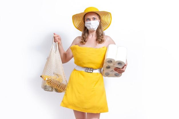 Frau im gelben kissenkleid und im hut mit maske und netzeinkaufsbaumwolltasche. mangel an essentiellen produkten. kauf gegen spende. pillow challenge wegen isolation zu hause bleiben.