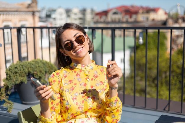 Frau im gelben kleid auf der terrasse im sommercafé mit handy am sonnigen tag, schauen glücklich und positiv mit großem lächeln auf gesicht
