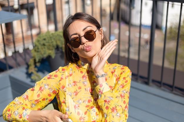 Frau im gelben kleid auf terrasse im sommercafé mit handy am sonnigen tag, schauen glücklich und positiv senden luftkuss