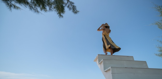 Frau im gelben kleid, das oben auf der treppe im sonnenuntergang geht.