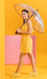 Frau im gelben kleid mit einem regenschirm