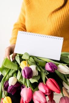 Frau im gelben pullover mit blumenstrauß der frischen rosa tulpen und des leeren kalenders