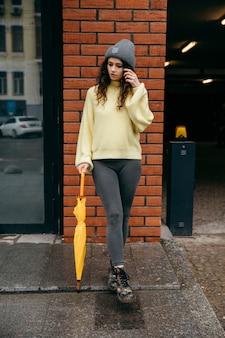 Frau im gelben pullover mit gelbem regenschirm bleiben an der wand