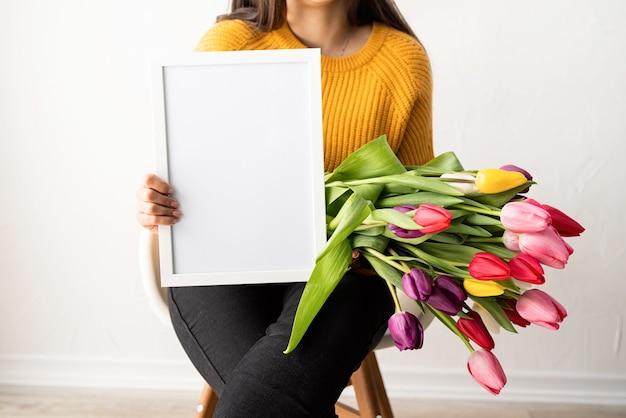 Frau im gelben pullover mit strauß der frischen rosa tulpen und des leeren rahmens