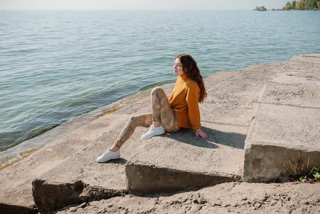 Frau im gelben pullover sitzt auf einer steintreppe am strand