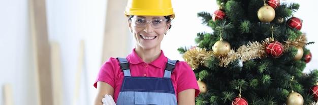 Frau im gelben schutzhelm und im bauoverall lächelnd im büro nahe neujahrsbaum. rabatte auf renovierungen vor weihnachten konzept
