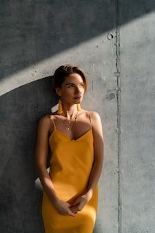 Frau im gelben sommerkleid mit kurzhaarfrisur im innenraum betonwand posiert