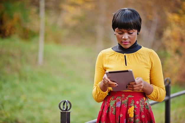 Frau im gelben und roten kleid am goldenen herbstfallpark mit tablette an den händen