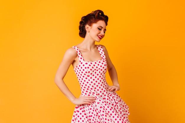 Frau im gepunkteten kleid, das mit lächeln aufwirft. romantisches pinup-mädchen, das auf gelbem raum lacht.