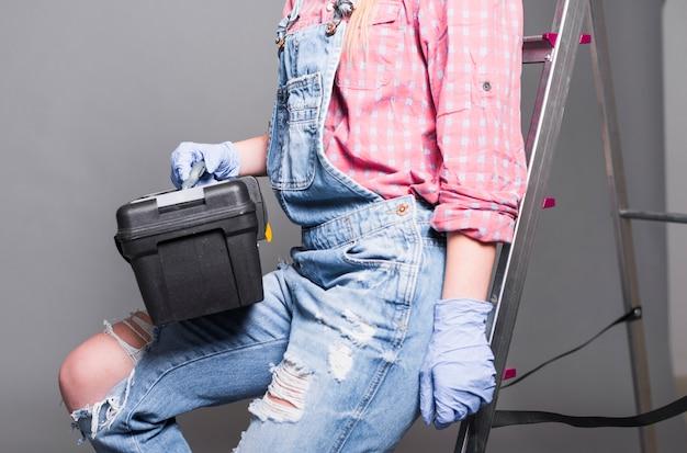 Frau im gesamtsitzen auf strichleiter mit werkzeugkasten