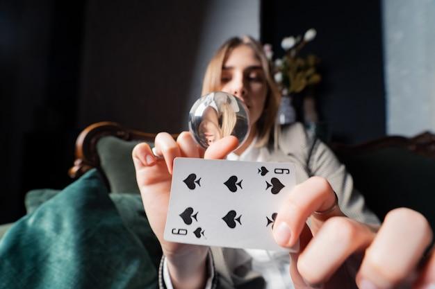 Frau im geschäftsanzug, der kristallkugel und sechs spaten in ihren händen hält