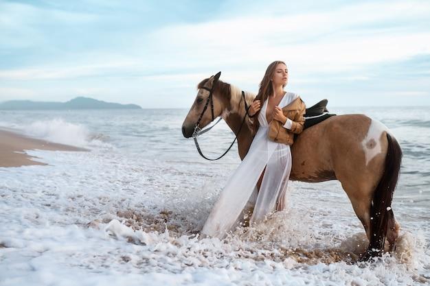 Frau im gesellschaftsanzug im ozean mit pferd, zeitbelichtung, die bewegung von wellen zeigt