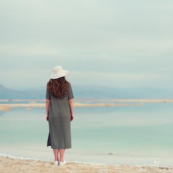 Frau im gestreiften kleid des seemanns nahe küste des strandes vom toten meer