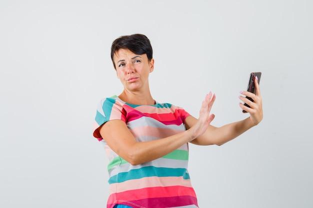Frau im gestreiften t-shirt unter verwendung des mobiltelefons beim zeigen der ablehnungsgeste, vorderansicht.