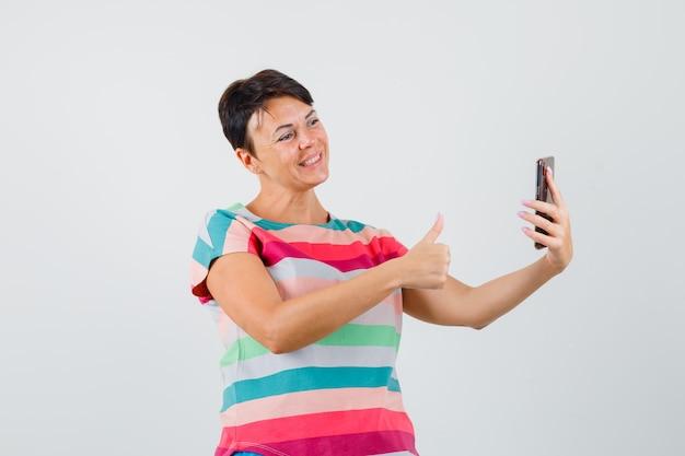 Frau im gestreiften t-shirt zeigt daumen oben auf video-chat und schaut fröhlich, vorderansicht.