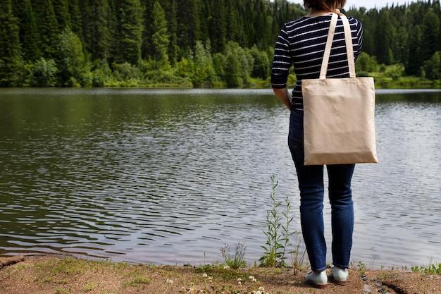 Frau im gestreiften t-stück, das leeres wiederverwendbares einkaufstaschenmodell trägt, blick auf den fluss.