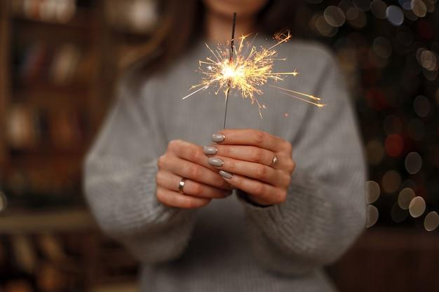Frau im gestrickten pullover feiert den feiertag mit erstaunlichen wunderkerzen in den weiblichen händen. nahansicht.