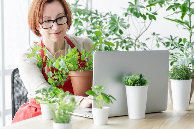 Frau im gewächshaus kümmert sich mit laptop um pflanzen in der nähe ihres arbeitsplatzes.