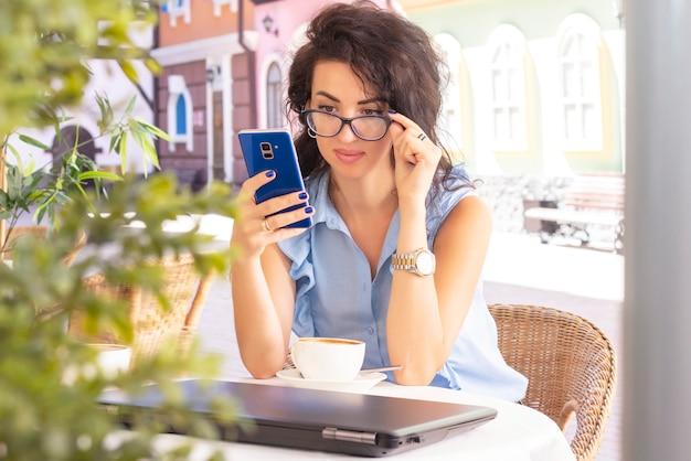 Frau im glas, das entfernt mit laptop und telefon im café arbeitet. schöne brünette mit notizbuch im café. glückliche geschäftsfrau, die auf handy anruft und nimmt. freiberuflich