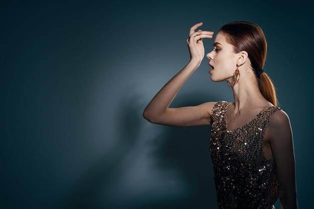 Frau im goldenen kleid dekoration glamour posiert studio