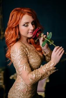 Frau im goldkleid, das rose in den händen hält und lächelt
