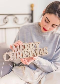 Frau im grau, das hölzerne aufschrift der frohen weihnachten hält