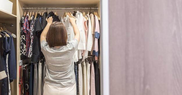 Frau im großen begehbaren kleiderschrank, der kleidung, moderne garderobe und umkleidekabine wählt
