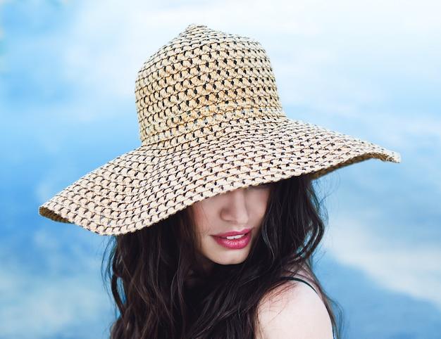 Frau im großen strohhut am sandstrand an einem sonnigen tag
