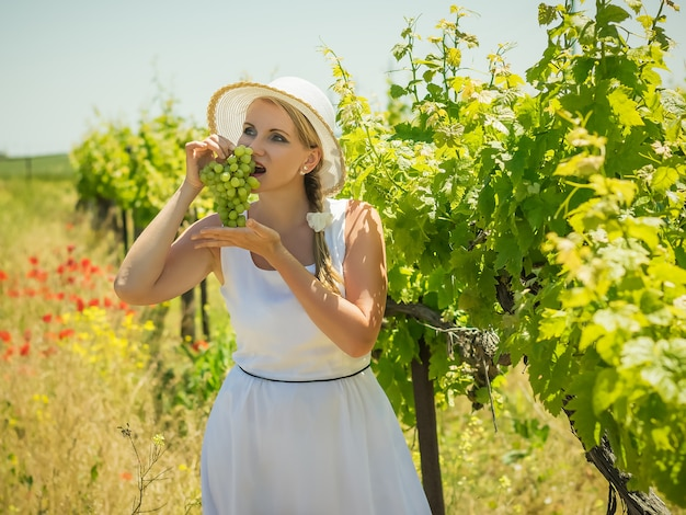 Frau im großen weißen hut isst grüne trauben auf dem feld.