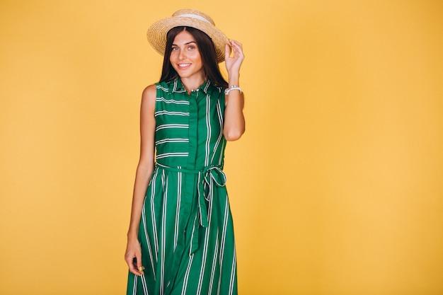 Frau im grünen kleid und im hut auf gelbem hintergrund