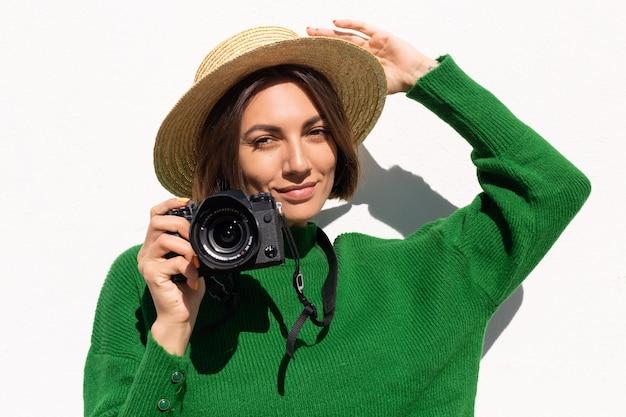 Frau im grünen lässigen pullover und hut im freien auf weißer wand glücklich positiver tourist mit professioneller kamera