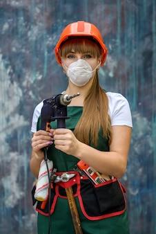 Frau im grünen overall und in der schutzmaske, die bohrmaschine auf abstraktem hintergrund hält
