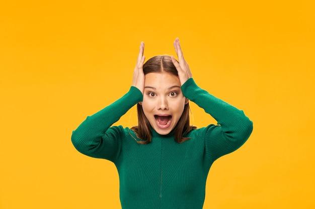 Frau im grünen pullover, der ihr kopfmodell mit gelbem hintergrund hält