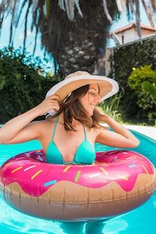 Frau im gummiring, der im pool steht