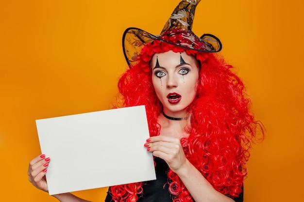 Frau im halloween-kostüm, das ein weißes blatt papier hält.