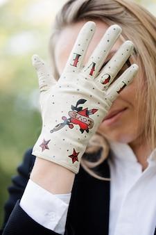 Frau im handschuh bedeckte ihr gesicht mit der hand