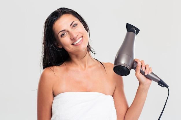 Frau im handtuch, das haartrockner hält