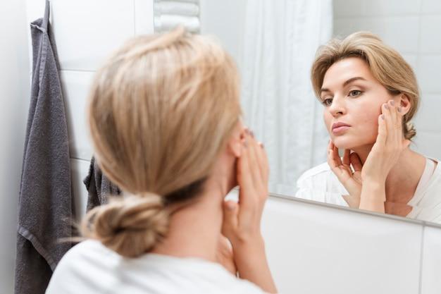 Frau im handtuch, die sich im spiegel prüft