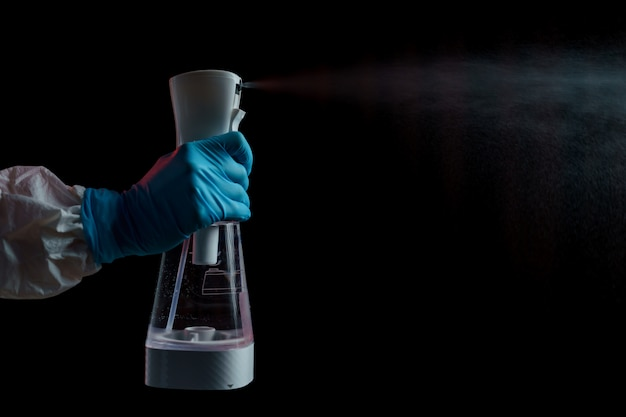 Frau im hazmat-anzug und im op-handschuh desinfiziert mit desinfektionsspray. coronavirus oder covid-19-schutz.