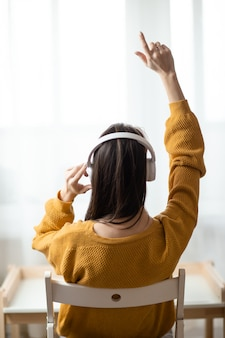 Frau im heimbüro während der selbstisolation, die von zu hause aus arbeitet. online-bildung, e-learning während der quarantäne. frau hört musik in weißen kabellosen kopfhörern.