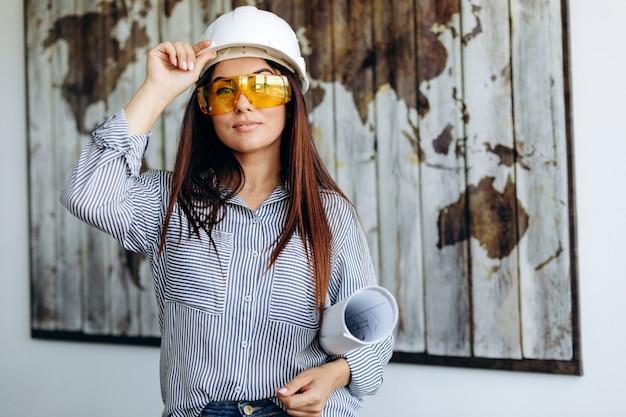 Frau im helm und blaupausen im büro arbeiten