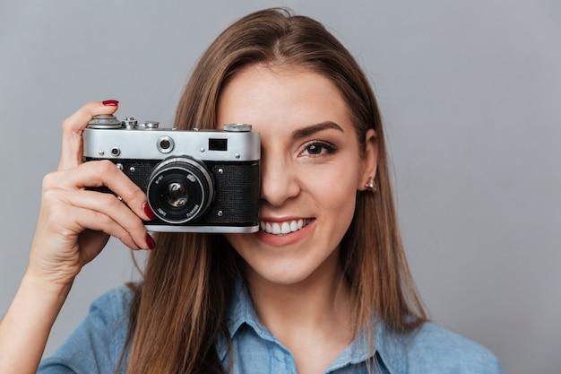 Frau im hemd, das telefon auf retro-kamera macht