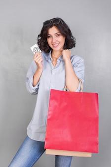 Frau im hemd mit kreditkarte und einkaufstaschen